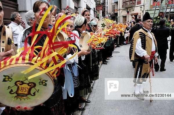 A man dressed in traditional costume of Llanes,  with women who play the tambourine during the arrival of the procession to the chapel of San Roque. Llanes,  Asturias,  Spain.