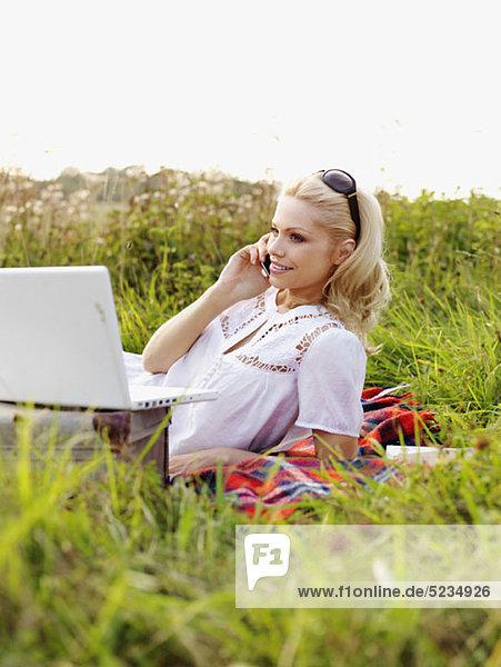Eine Frau in der Natur mit offenem Laptop und Handy