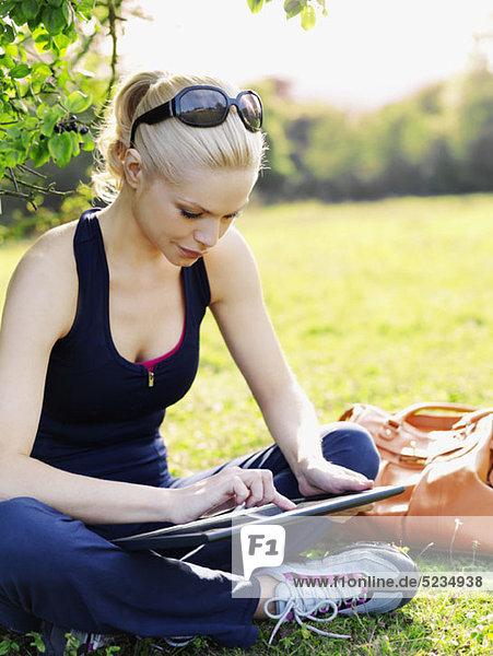 Eine Frau in Sportbekleidung  die im Gras sitzt und ein digitales Tablett benutzt.