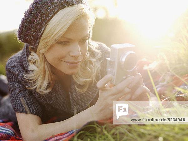 Eine Frau beim Fotografieren im Gras liegend
