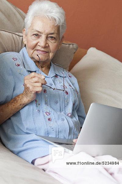 Eine ältere Frau sitzt auf einem Sofa mit einem Laptop.