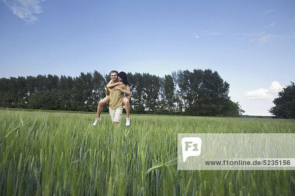 Ein Mann  der seine Freundin huckepack durch ein Weizenfeld fährt.