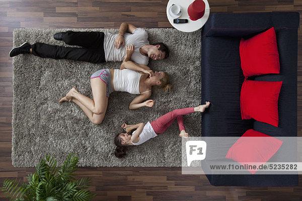 Eine dreiköpfige Familie  die glücklich auf einem Wohnzimmerteppich liegt.