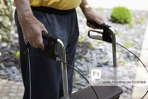 Ein älterer Mann steht mit einem Geher  in der Mitte  im Freien.