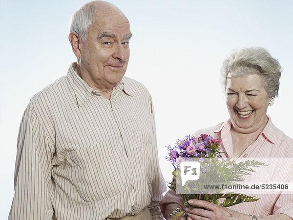 Der ältere Mann weiß  dass sie glücklich ist  wenn er ihr Blumen schenkt.