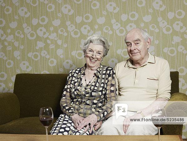 Mann und Frau entspannt auf dem Sofa  mit zwei Gläsern Rotwein auf dem Tisch davor