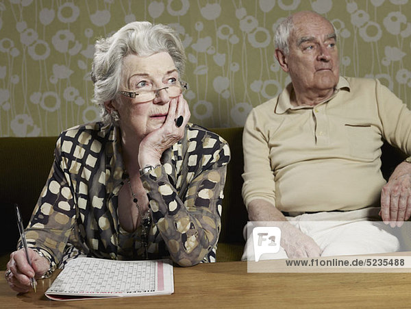 Senior woman works out magazine puzzle with senior man in background