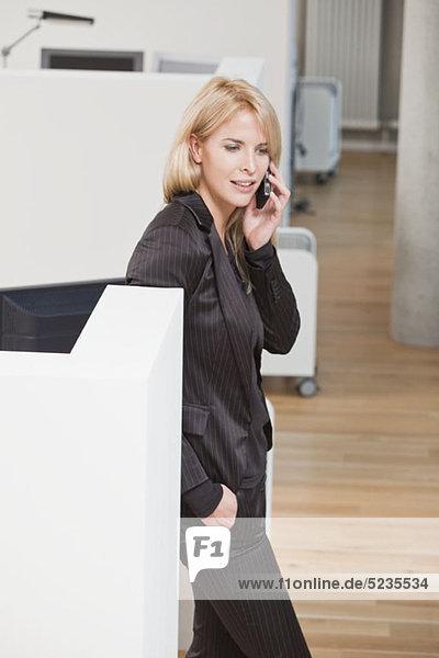 Geschäftsfrau lehnt sich auf dem Handy gegen die Bürozelle