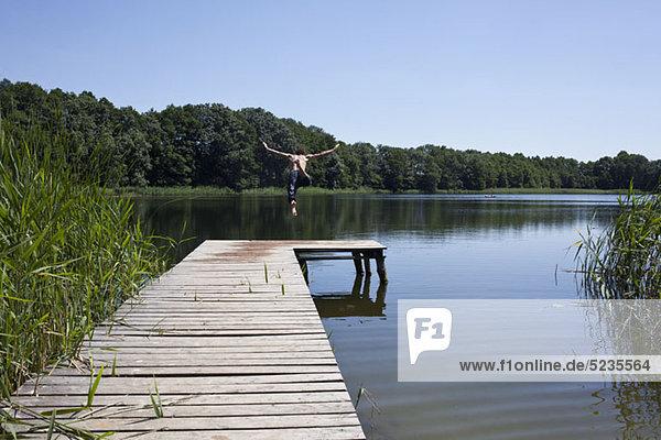 Der Typ am Steg taucht mit ausgestreckten Armen in den See.