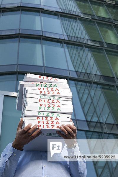 Mann mit Pizzakartons vor seinem Gesicht Mann mit Pizzakartons vor seinem Gesicht