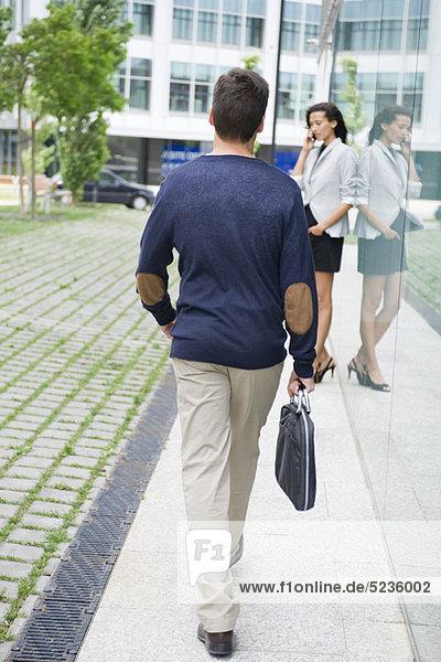 Mann geht mit Aktentasche  Frau spricht auf dem Handy im Hintergrund