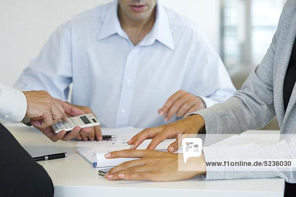 Führungskräfte bei Geschäftsgesprächen mit dem Taschenrechner