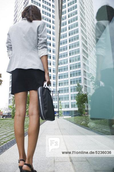 Frau auf dem Bürgersteig stehend mit Aktentasche  Blickwinkel niedrig