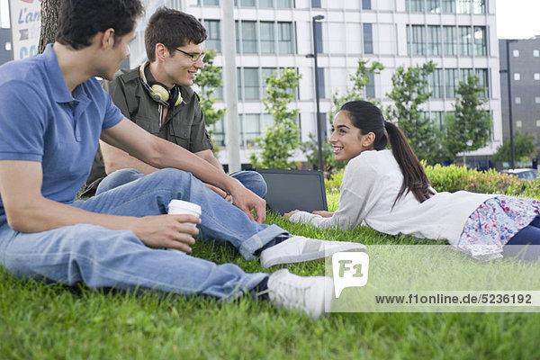 Freunde  die sich gemeinsam auf Rasen entspannen