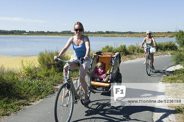 Mehrgenerationen-Familie genießt Fahrradfahren  Kinder sitzen im Fahrradanhänger