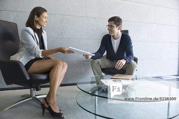 Geschäftsfrau bei der Übergabe der Dokumente an den Kunden