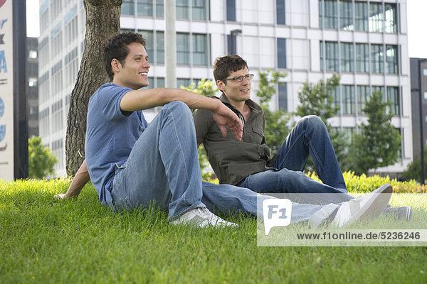 Männer sitzen im Gras in der Stadt