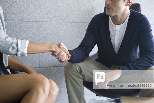 Mann und Frau beim Händeschütteln  Mittelteil
