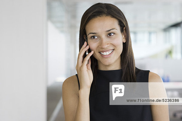 Smiling woman talking on cell phone  portrait