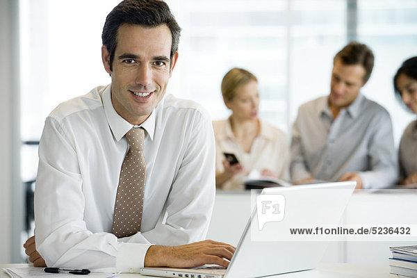 Lächelnder Geschäftsmann mit Laptop-Computer