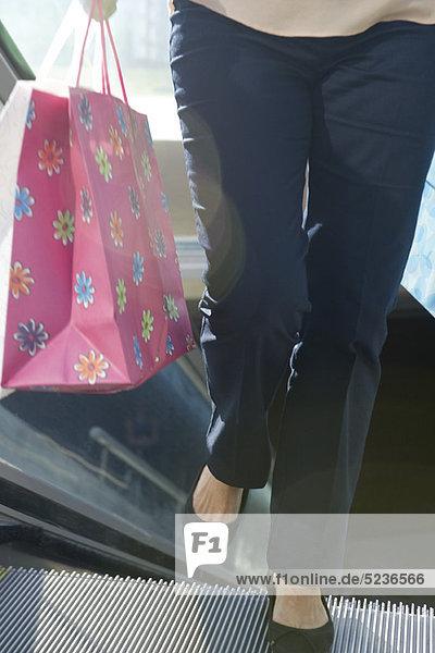 Frau auf Rolltreppe mit Einkaufstaschen  niedrige Sektion