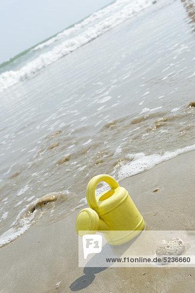 Spielzeug-Gießkanne am Strand