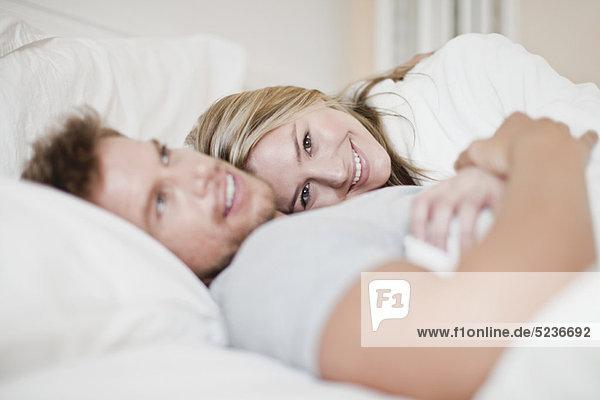 Lächelndes Paar entspannt im Bett