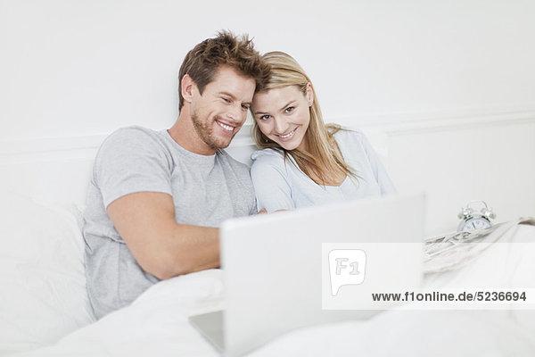 Lächelndes Paar mit Laptop im Bett