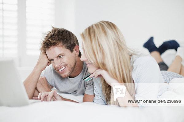 Lächelndes Paar beim Online-Shopping im Bett