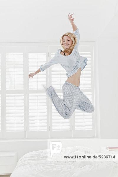 Frau springt auf Bett