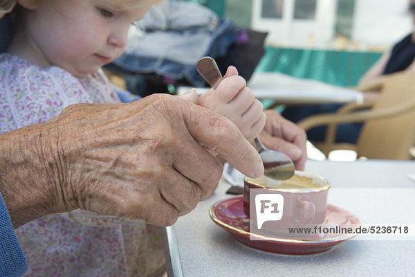Kleinkind Mädchen hilft Großmutter rühren Tasse Kaffee  abgeschnitten