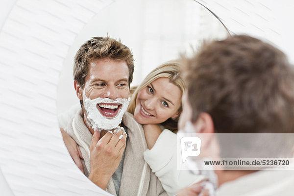 Frau schaut dem Freund beim Rasieren zu.