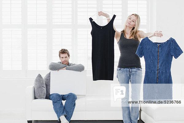 Frau beim Aussuchen von Kleidung im Wohnzimmer