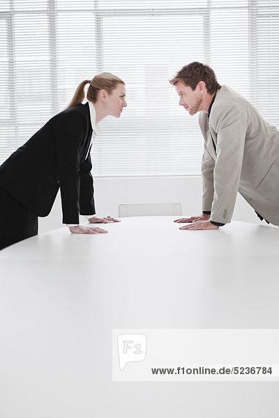 Rivalisierende Geschäftsleute  die sich über den Schreibtisch lehnen.