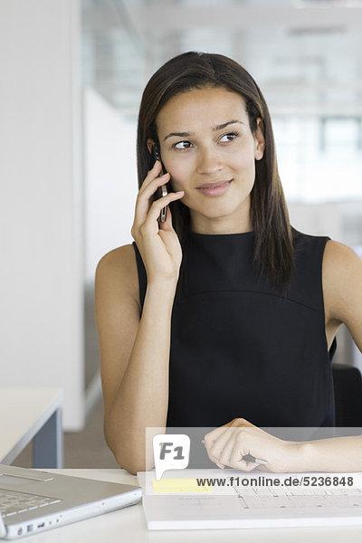 Frau am Schreibtisch mit Blaupause  spricht auf dem Handy