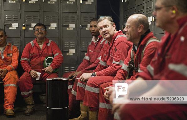 Arbeiter sitzen in der Umkleidekabine
