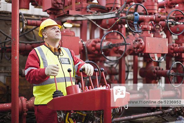 Arbeiter  der Maschinen auf einer Bohrinsel betreibt