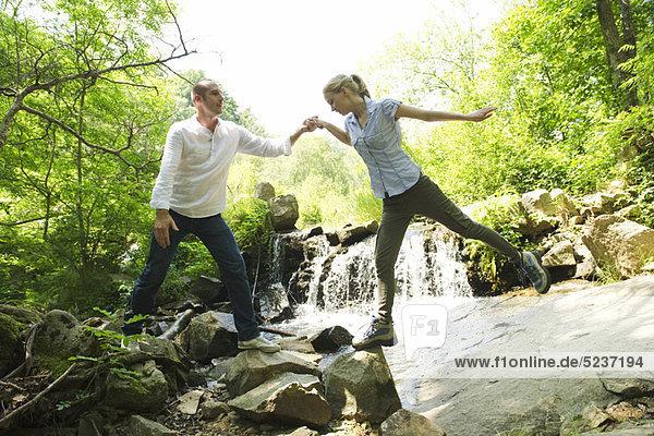 Couple Standing auf Felsen von Wasserfall