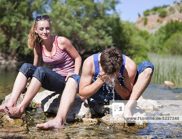 sitzend  Jugendlicher  Felsen  Fluss