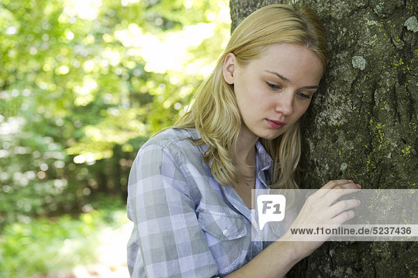 Young Woman leaning against Baum  looking traurig