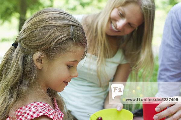 Mädchen mit ihren Eltern im Freien entspannen