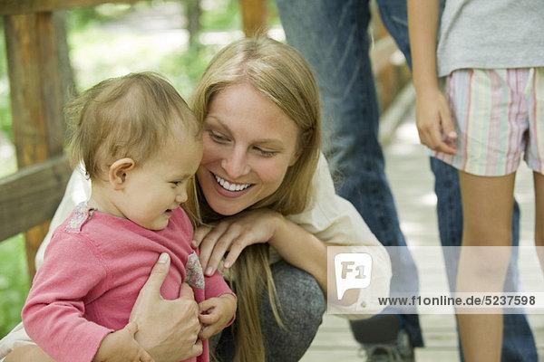 Mutter hocken neben Baby im freien