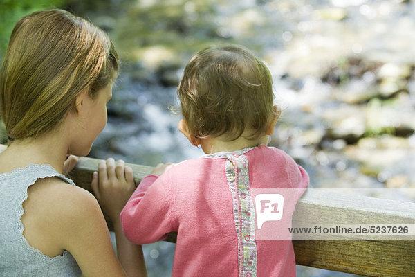 Mädchen und Baby Schwester über Geländer  Rückansicht