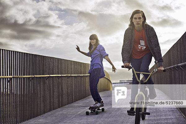 Jugendliche beim Radfahren und Skateboardfahren