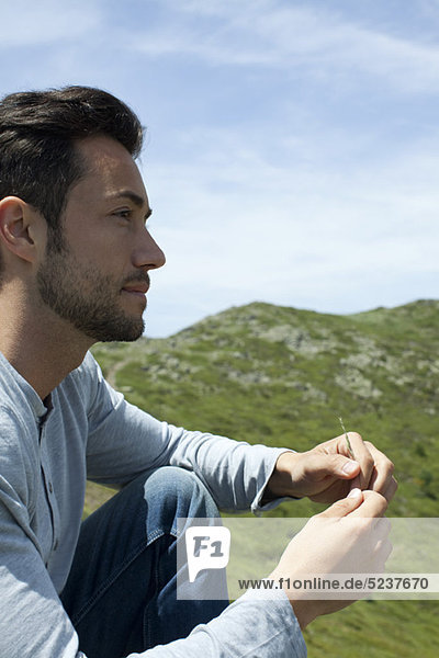 Man sitting outdoors  looking away in thought
