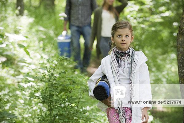 Mädchen zu Fuß im Wald mit Eltern  Blick nach oben