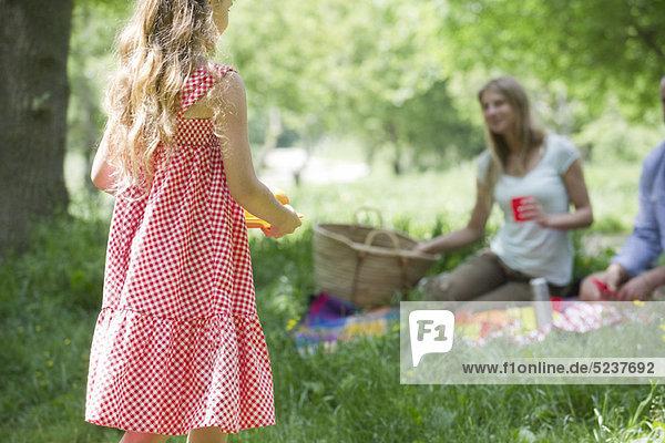 Kleines Mädchen mit Picknick mit Familie