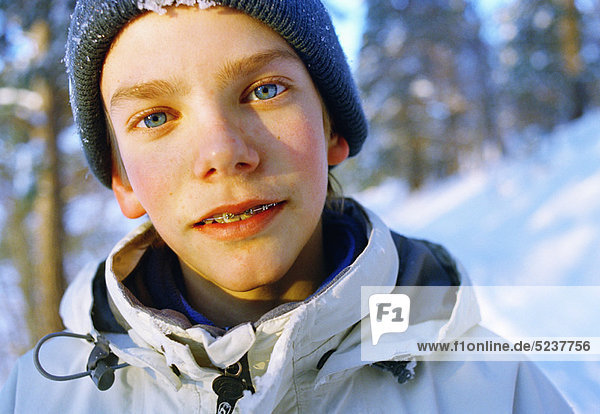 Close up of boy with braces in parka