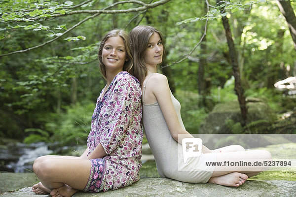 Freundinnen  die Rücken an Rücken sitzend auf einem Felsen  Porträt Freundinnen, die Rücken an Rücken sitzend auf einem Felsen, Porträt