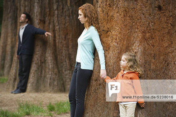 Mutter und Tochter gelehnt Baum  Vater stehen separate im Hintergrund